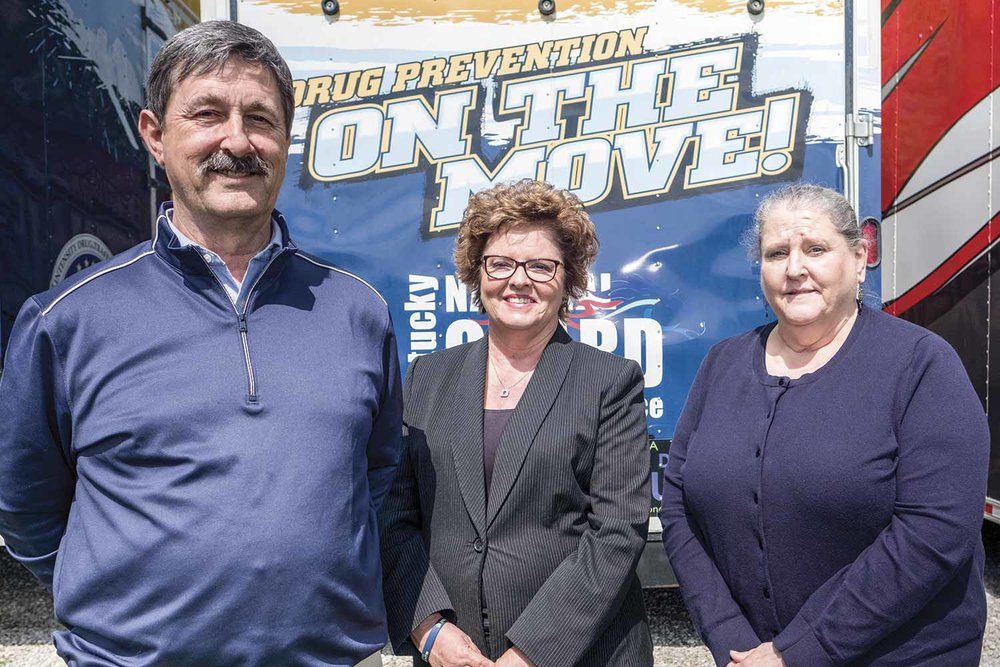 (L-R) UNITE Deputy Director Tom Vicini, President Nancy Hale and Education and Treatment Director Debbie Trusty stand in front of the organization's On the Move trailer. The trailer is used to travel throughout UNITE's district teaching students about drug and alcohol impairment and the dangers of abuse and addiction. (Photo by Jim Robertson)