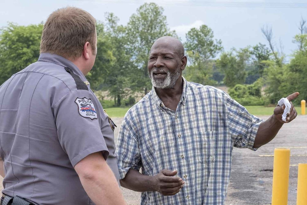 Hickman Police Chief Tony Grogan interacts with local resident, Alvin, outside city hall. (Photo by Jim Robertson)