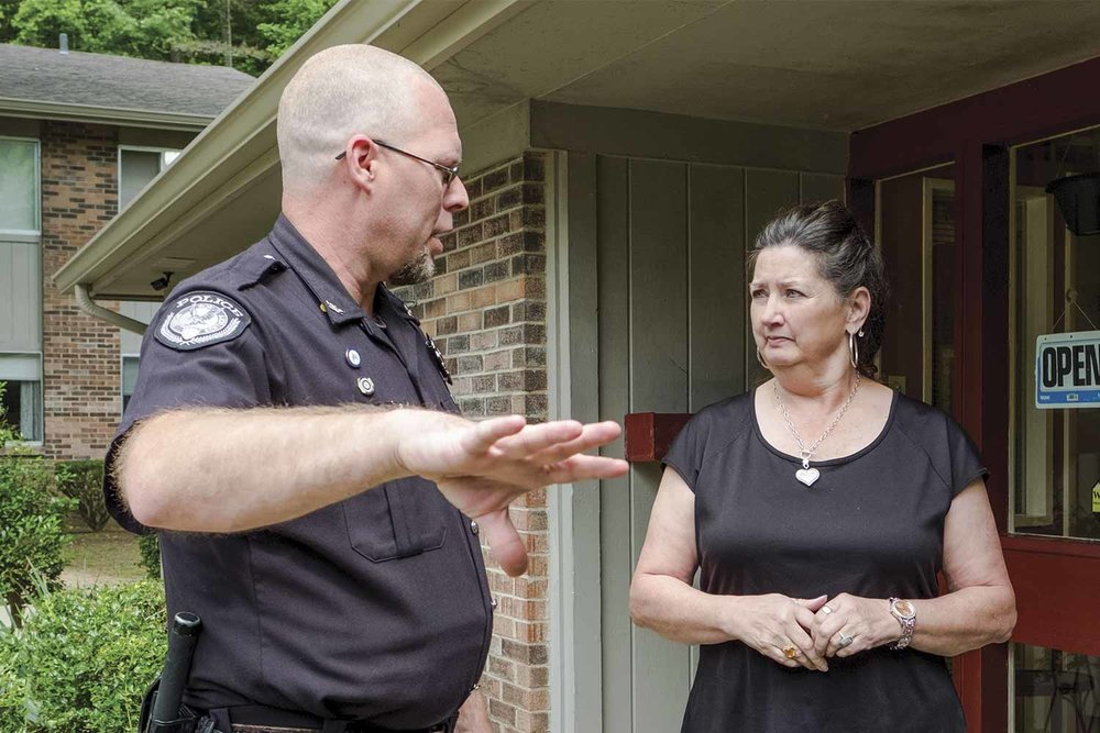 McKee Police Chief Jonathon Sizemore speaks with Jackson Valley Apartments manager Carolyn Going about a burglary at one of the units in early June. (Photo by Jim Robertson)