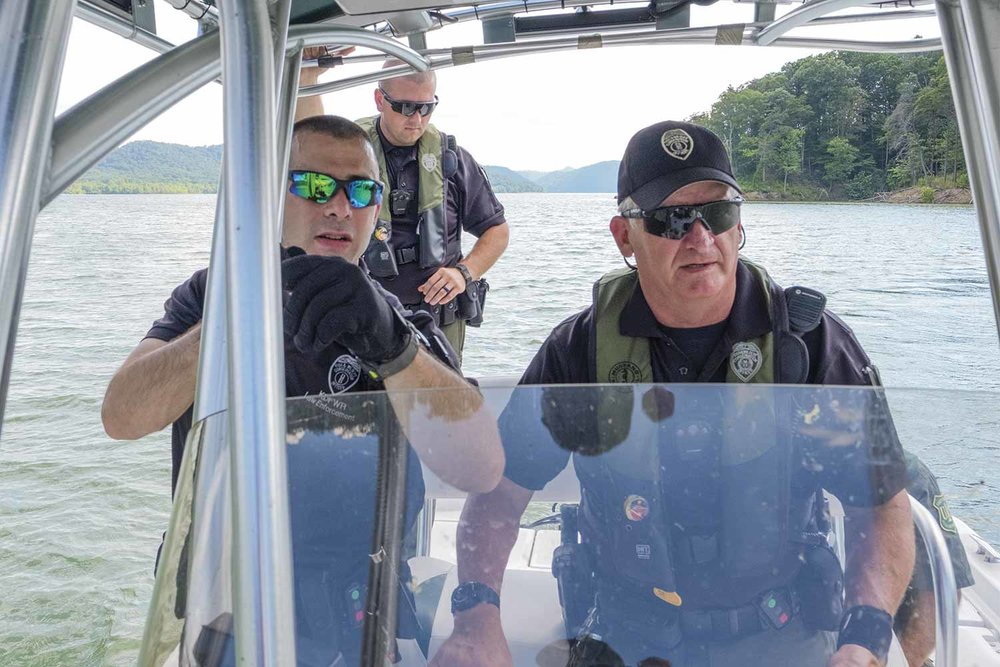 Conservation officer Brad Stafford, front, left, Sgt. Glenn Kitchen, front, right, and conservation officer Christopher Carson took to the waters of Cave Run Lake to search for Gary Hogston after the suspect eluded capture earlier in the day. (Photo by Jim Robertson)