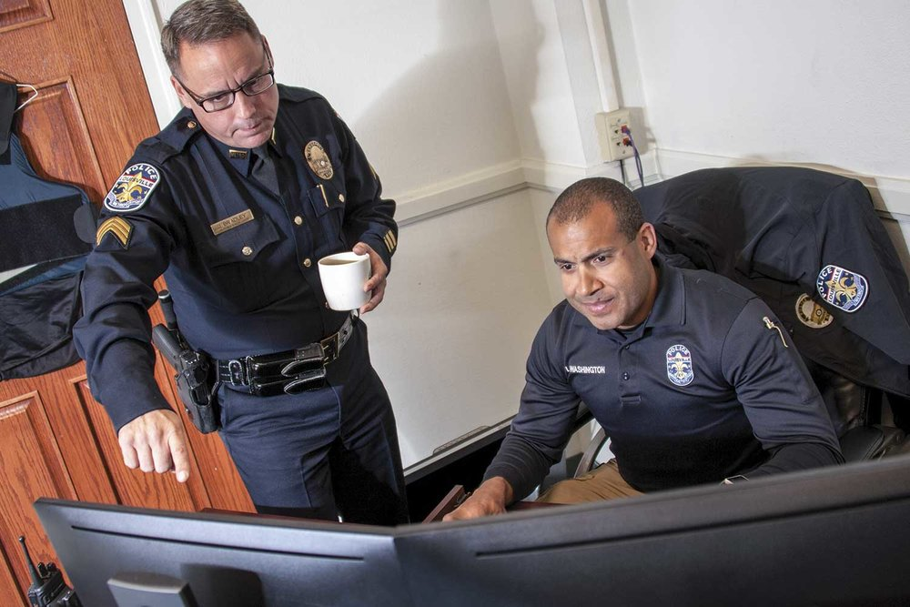 LMPD Sgt. John Bradley and Washington review edits of a video. (Photo by Jim Robertson)