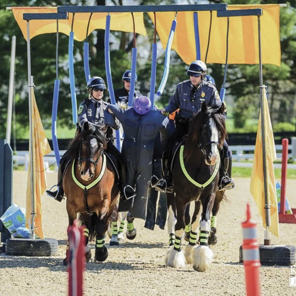 Kentucky Horse Park Troopers Julie Schmidt and Justin DeCecca conduct a demonstration of a prisoner escort during the 2018 Land Rover event held in April at the park. The event is the largest annual equine competition held at the Kentucky Horse Park. (Photo by Jim Shambhu / Kentucky Horse Park)
