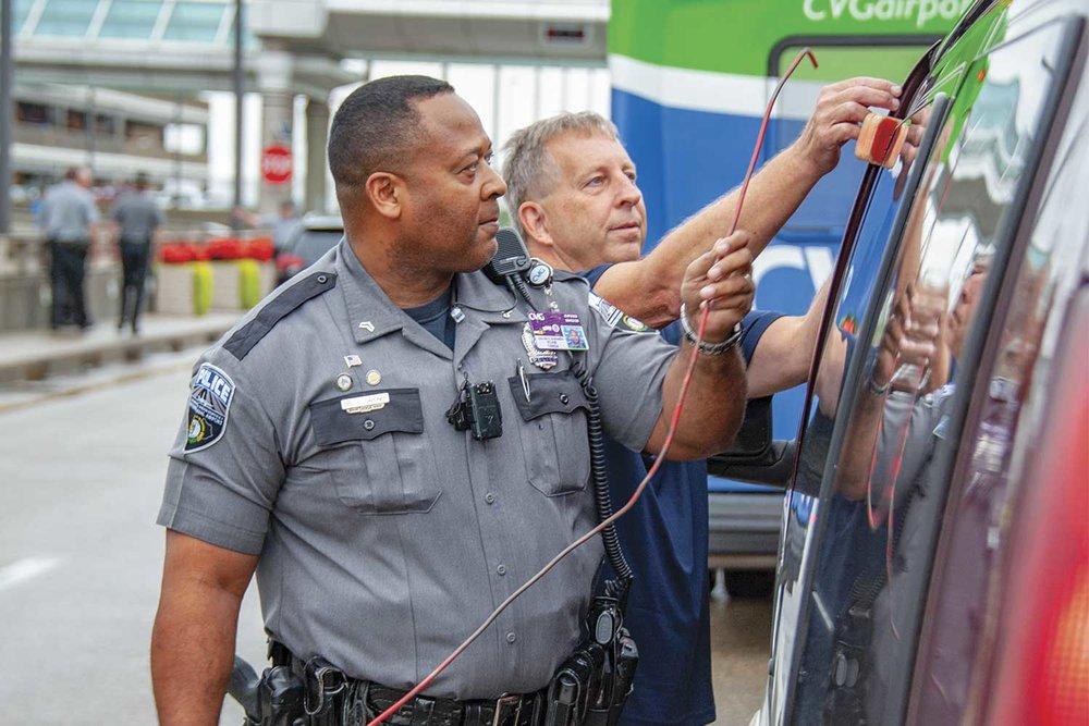 Cincinnati-Northern Kentucky International Airport Cpl. Calvin Gardner, left, helps a man unlock his van outside the main terminal. (Photo by Jim Robertson)