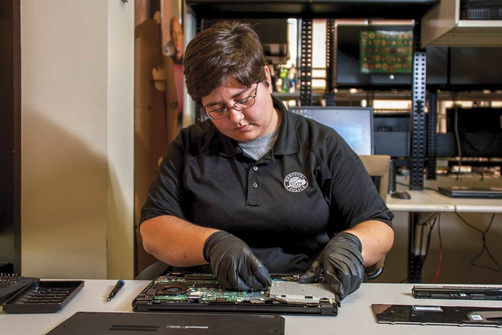 Forensics examiner Carol Smith inspects a hard drive for the Kentucky State Police Electronic Crimes Branch. She is one of five civilian forensics experts at the ECB. (Photo by Jim Robertson)