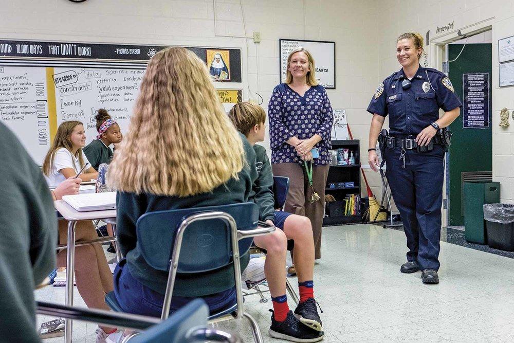 Owensboro Police Officer Jennifer Haynes, right, greets students at Owensboro Catholic Middle School alongside Principal Sara Guth. Haynes serves OCMS as part of Owensboro Police Department's adopt-a-school program. (Photo by Jim Robertson)