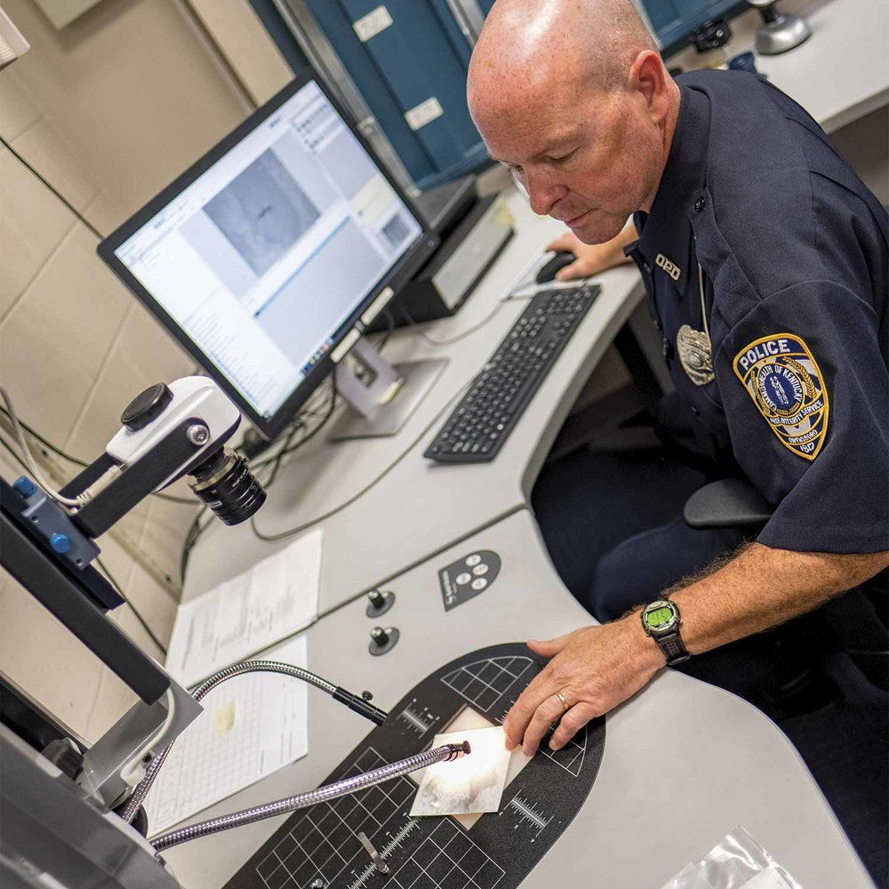 Owensboro Police Officer Jim Parham processes evidence using the department's Automatic Fingerprint Identification System, better known as AFIS. (Photo by Jim Robertson)