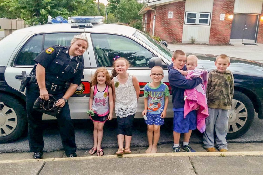 London Police Officer Ashley Taylor poses with several kids from the community she serves. The LPD officer said it's not uncommon for her to pull her cruiser over, get out and interact with children. (Photo provided)