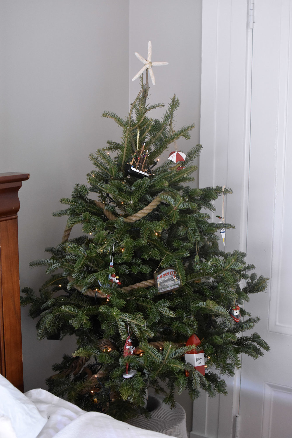 "A tabletop tree is trimmed with nautical ornaments from Nantucket, Martha's Vineyard and beyond, draped with a marine rope ""garland"" and topped with a starfish."
