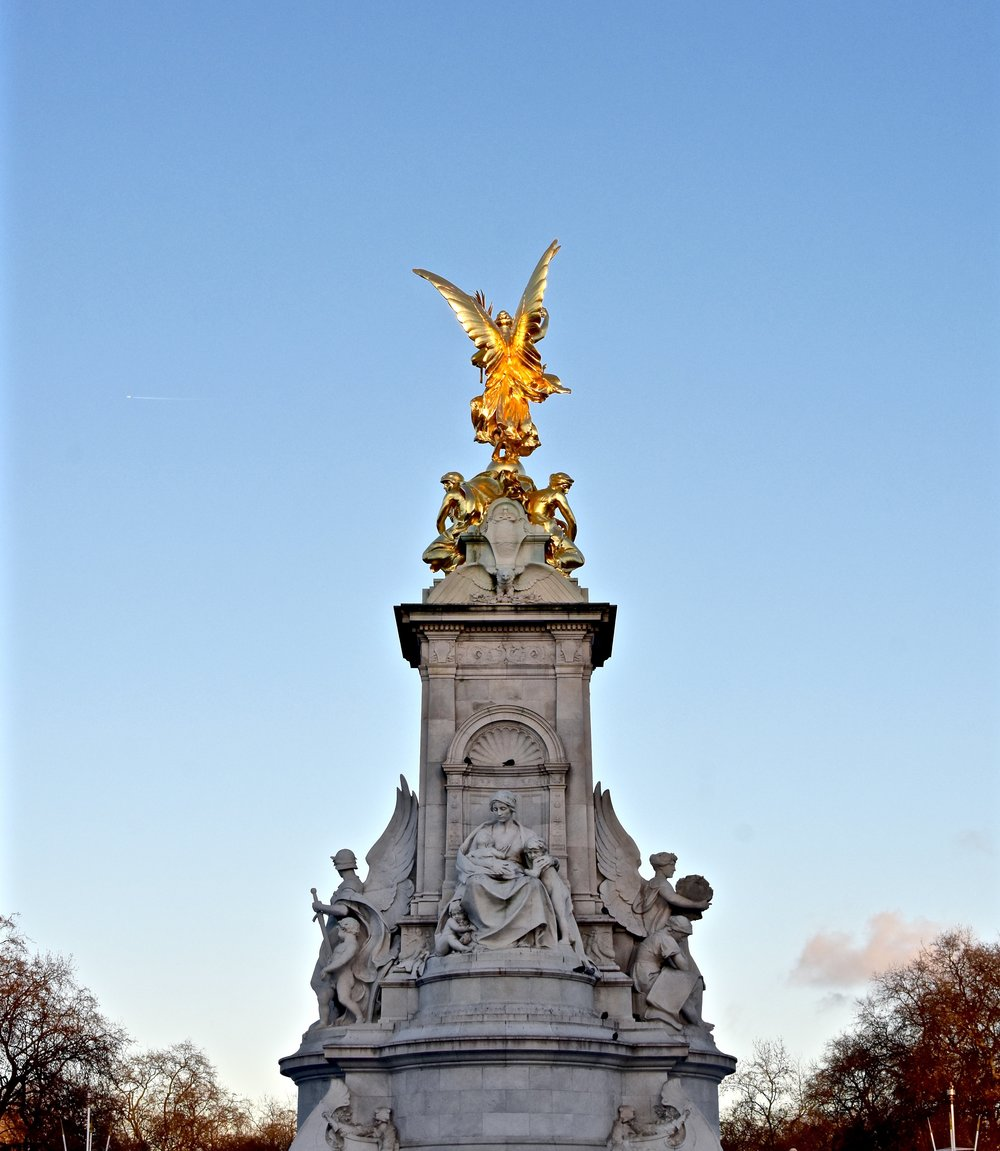 Atop the pediment of the heart-achingly lovely  Queen Victoria memorial , the gilded Winged Victory glows in the light of dusk as night settles over the city of London.
