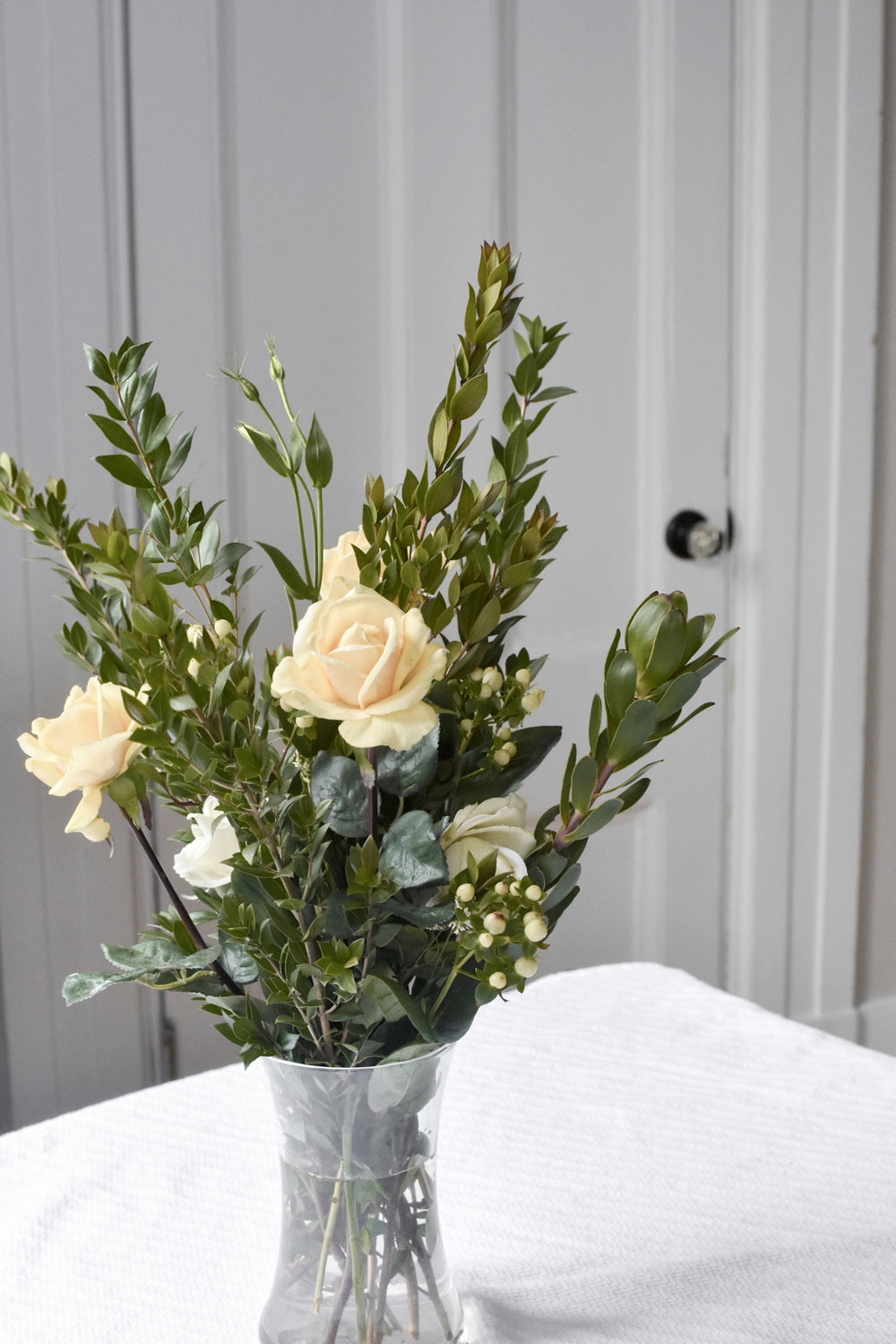 Faux roses pair beautifully with six-stem myrtle leaves and ivory hypericum berries.