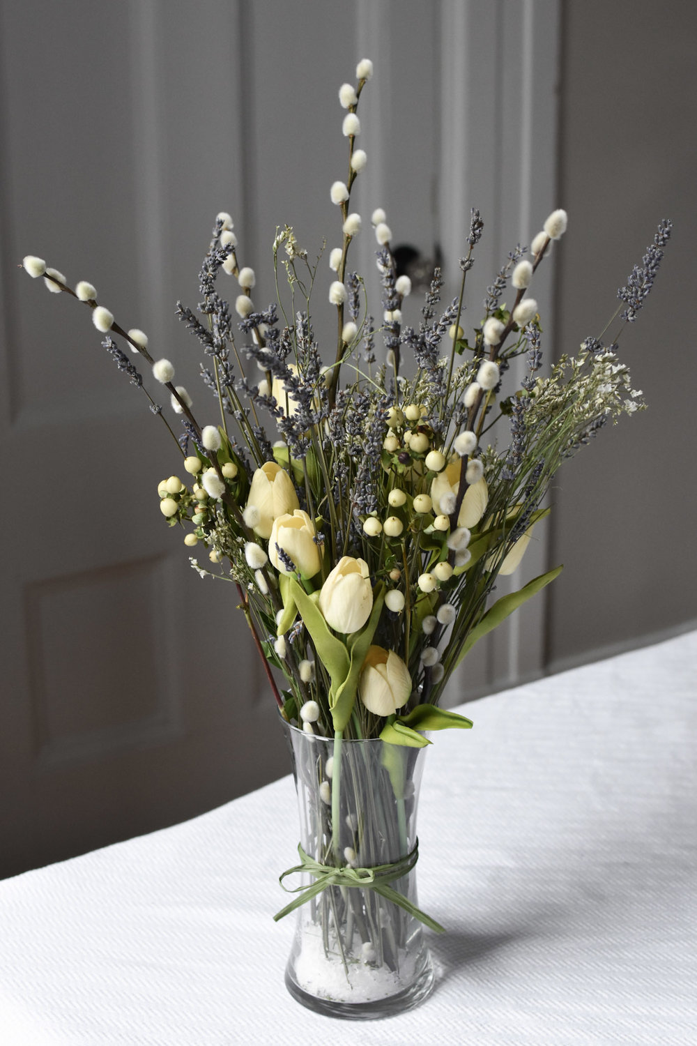 For a long-lasting arrangement that needs no watering, tuck faux tulips into a slender vase together with fragrant lavender, delicate limonium and a few branches of soft pussy willow.  Stems of hypericum berries may be added as well, just be sure to pinch off the leaves as they will otherwise wither to an unsightly brown.