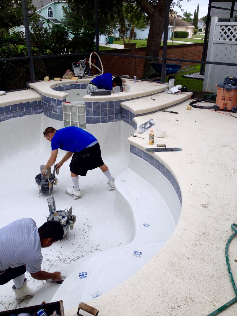 Plastering team finishing resurfacing of a pool