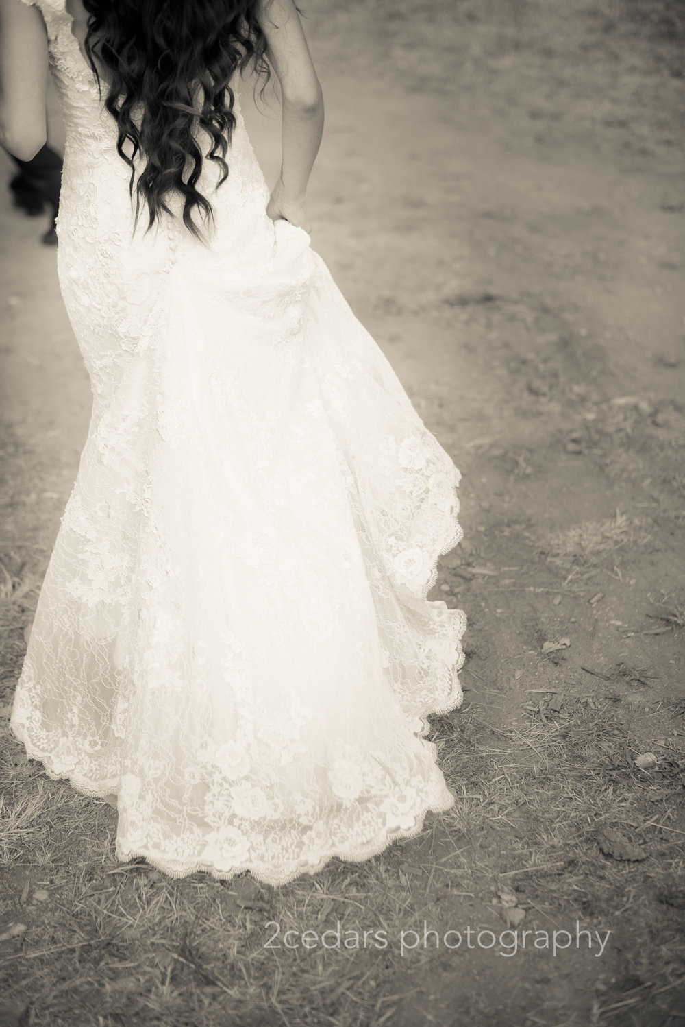 bride wedding gown train walking across the dirt road