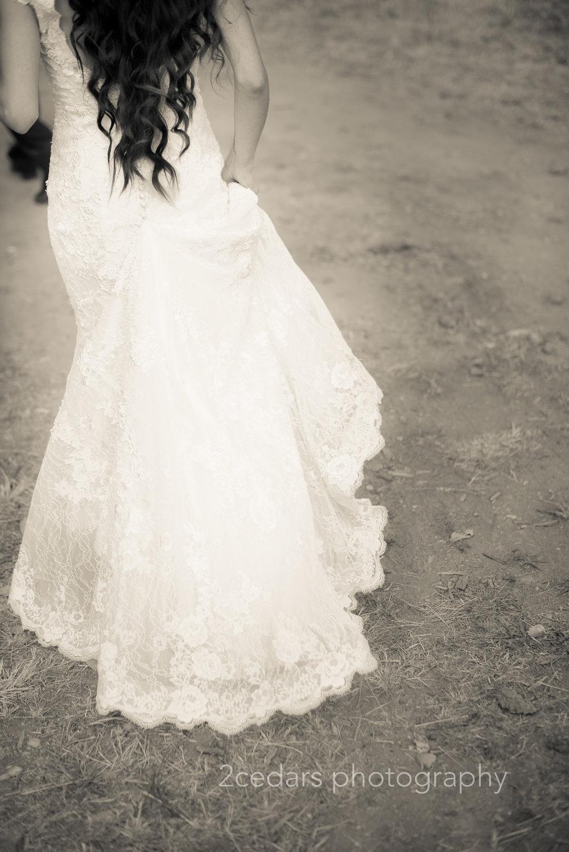 bride wedding gown train walking across the dirt road