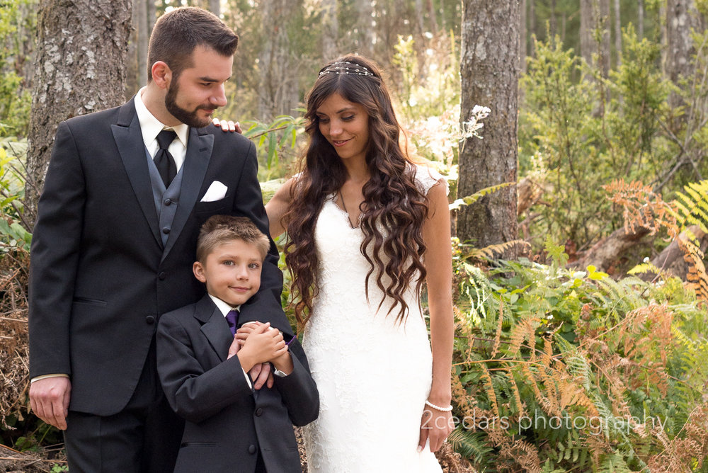 Bride and groom with son. Pacific Northwest wedding in the woods