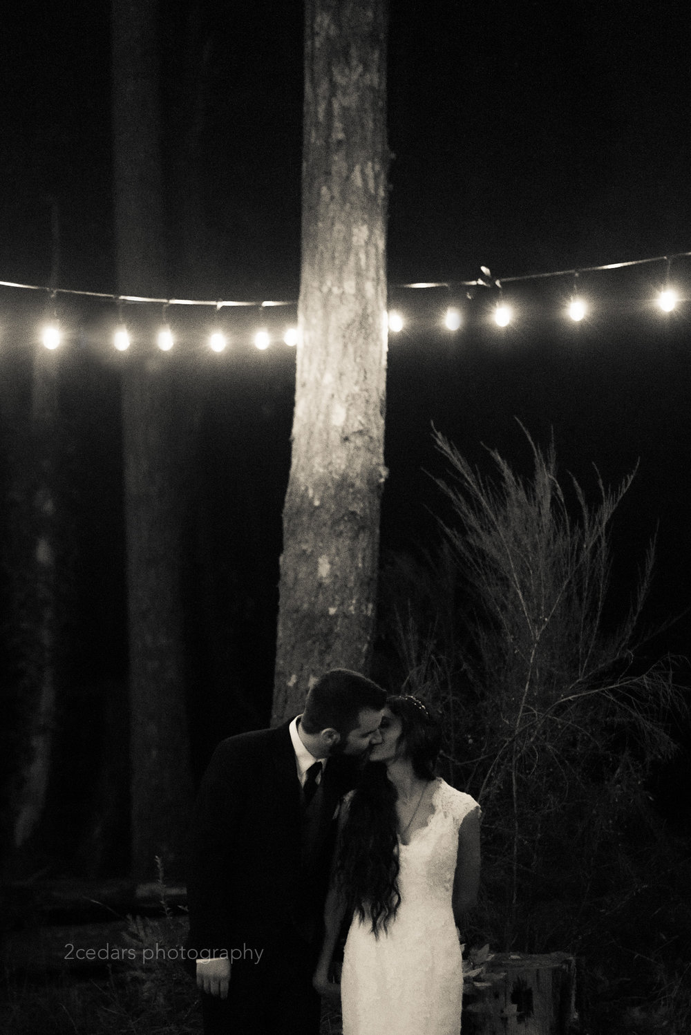 black and white bride and groom kiss under tree lights