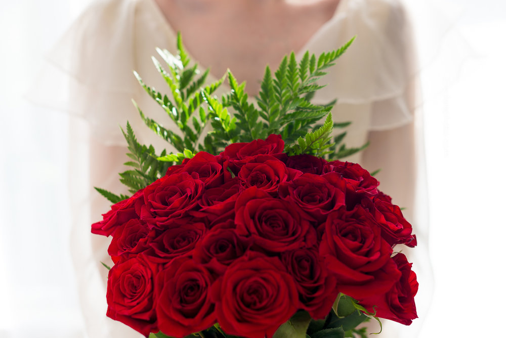 Bride with close up of bouquet of red roses and ferns