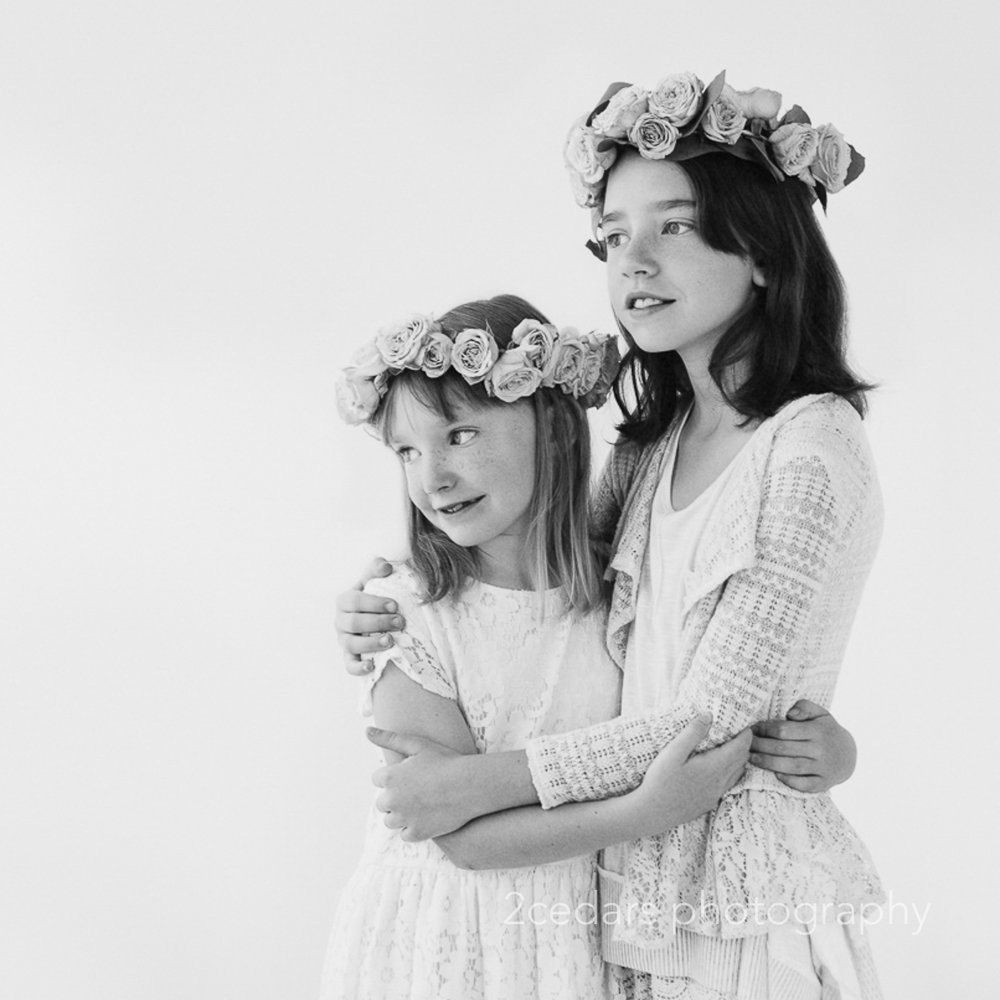 Black and white formal portrait of sisters in flower crowns