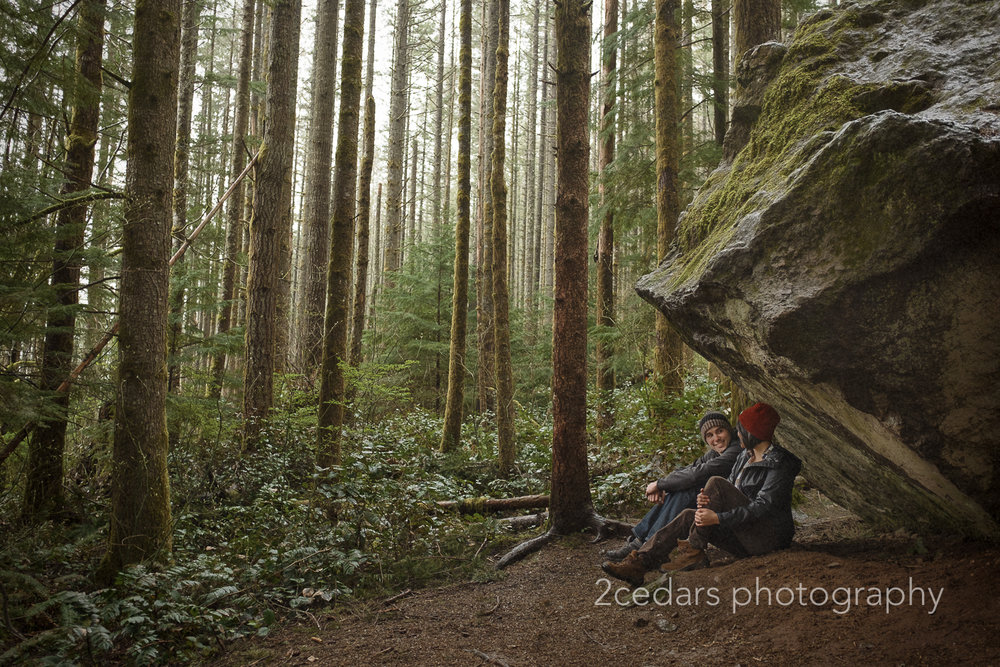 Couple under boulder in forest rain