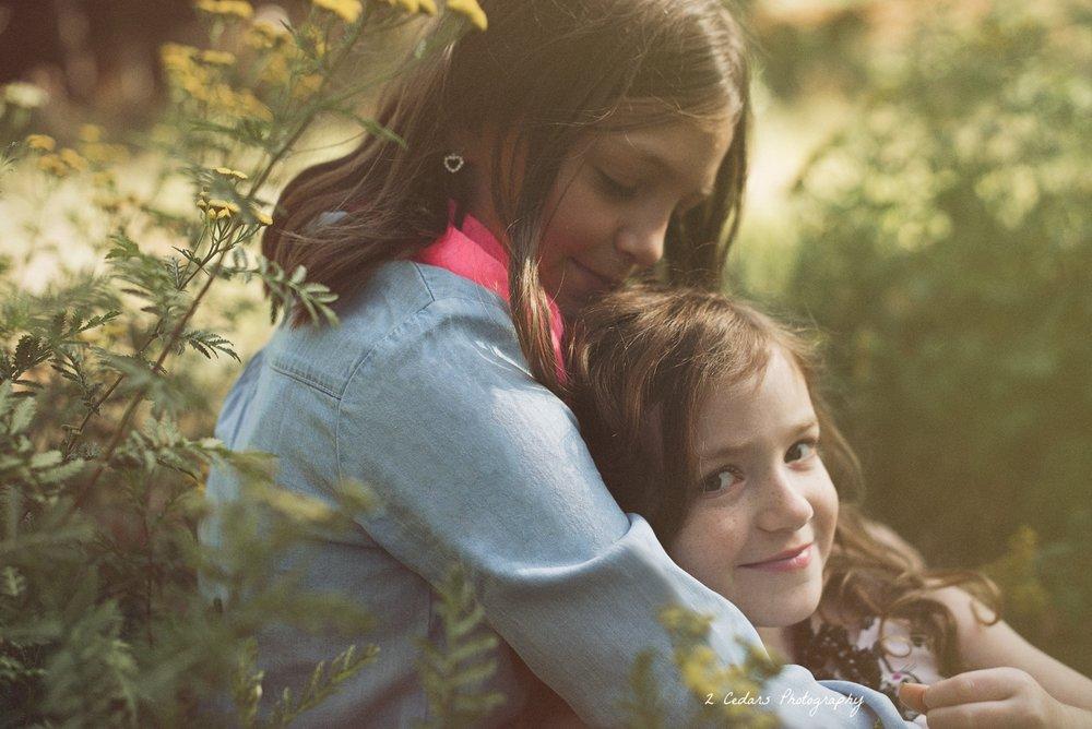 Sisters Hugging outdoor portrait in wildflowers