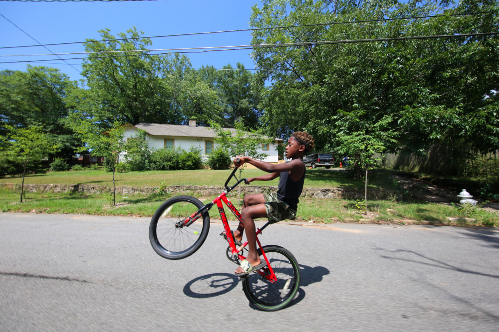 "ABOVE: Derrick McLemore, 10, practices ""walking"" his bike."