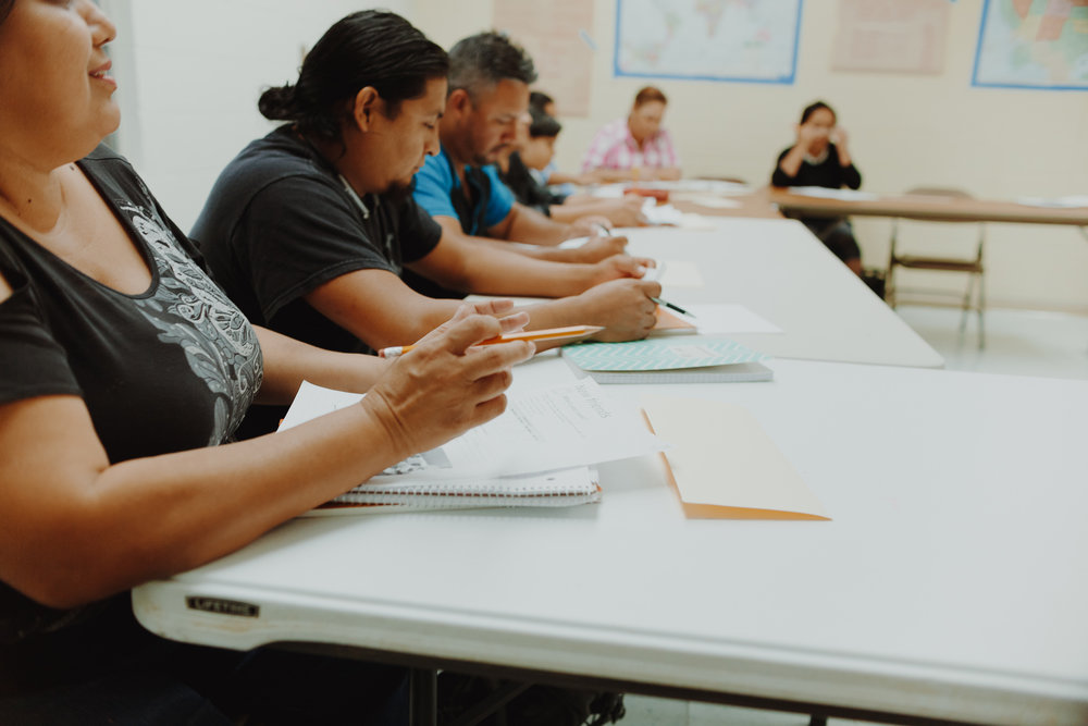 Volunteer Mark Wirtz talks through an exercise with his English as a Second Language (ESL) class. Immigrants take classes to gain confidence in their speaking, reading, and writing skills.