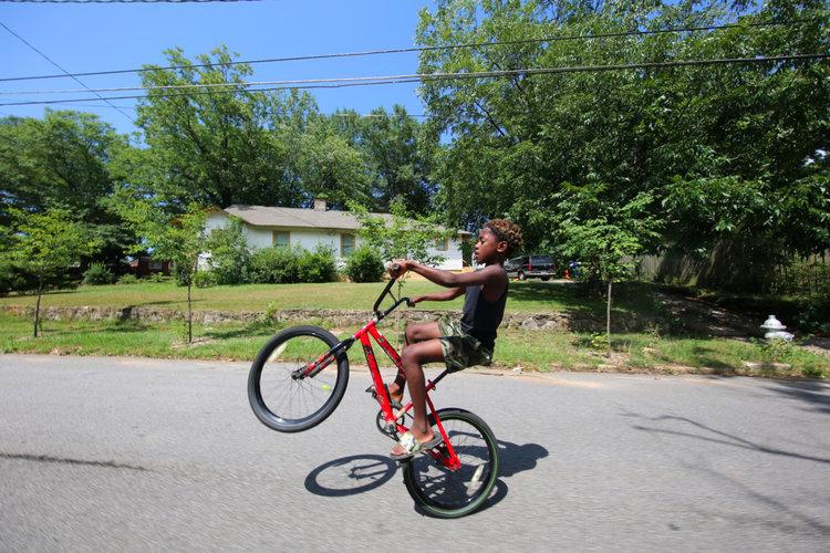 "ABOVE: Derrick McLemore, 10, practices ""walking"" his bike."