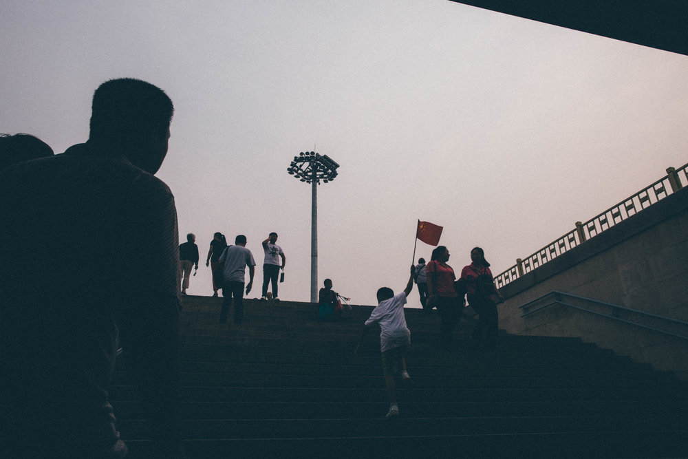 A young boy runs up the stairs to Tiananmen square waving the flag of the People's Republic of China. Beijing, China.
