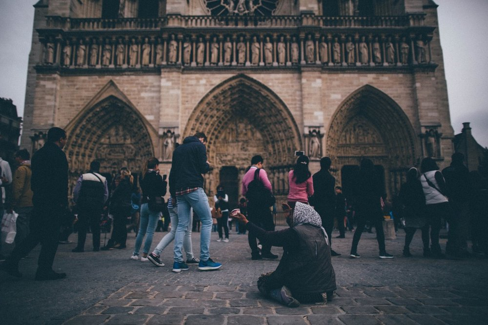 A woman begs for change as tourists wait to enter the Notre Dame Cathedral in the  fourth arrondissement. Paris, France