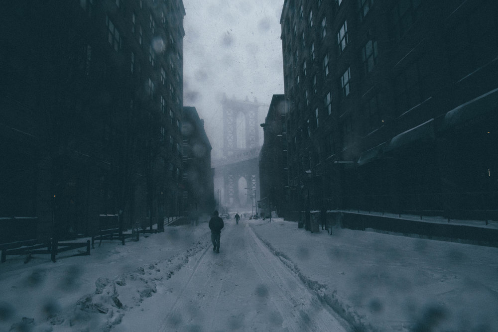 Pedestrians traverse the snowy streets of DUMBO during Blizzard Jonas. Brooklyn, New York.