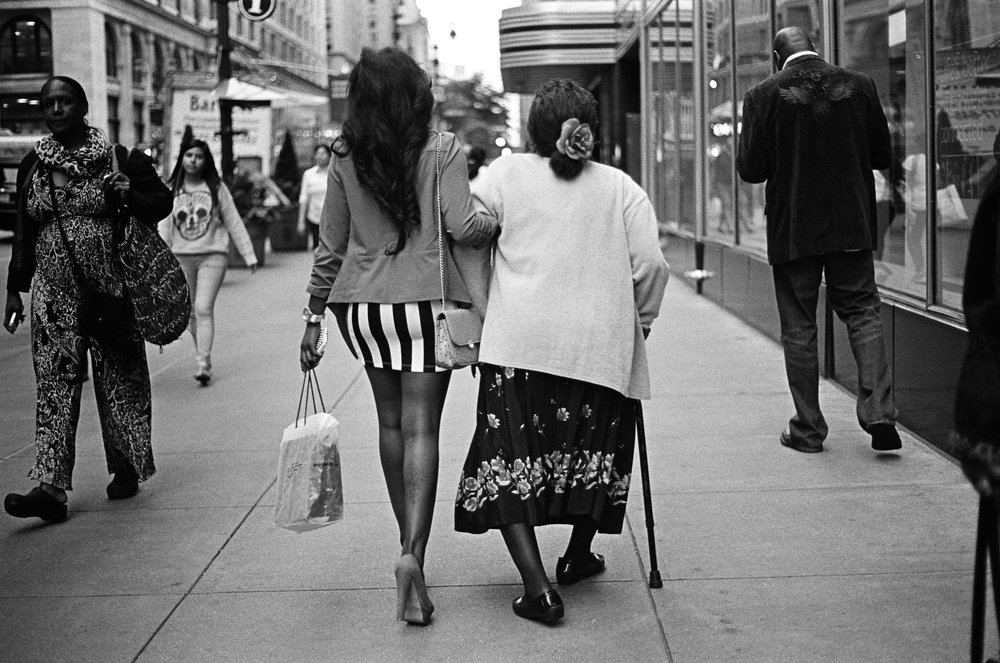A granddaughter helps her grandmother down 34th Street.