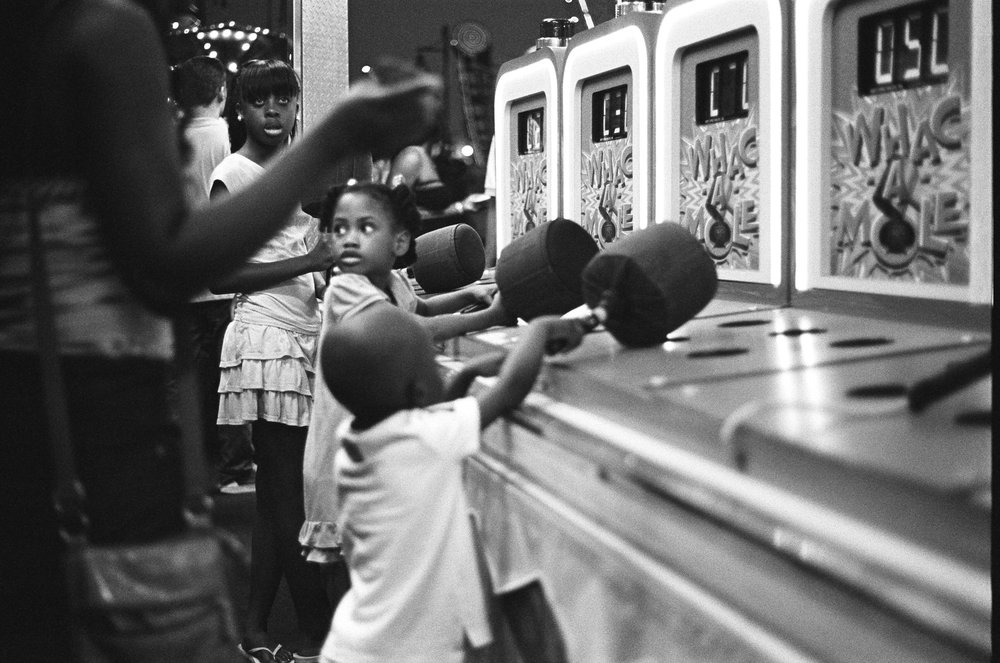 Siblings play Whack-A-Mole during a summer evening at Coney Island.