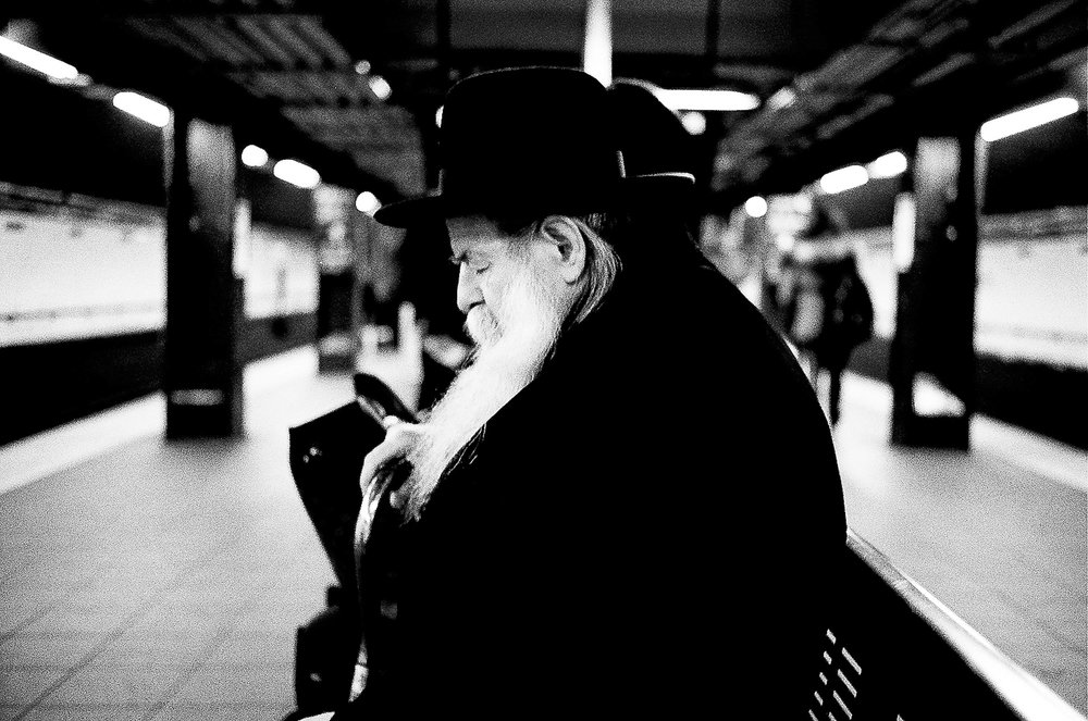 A Hasidic man takes a quick nap on the Fulton Street subway platform