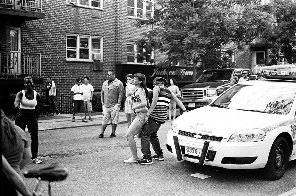 Teenagers dance on a NYPD car during a block party in Queens