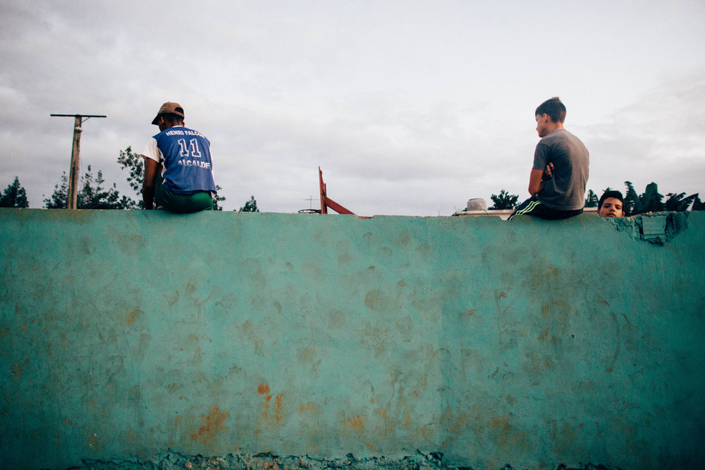 Three boys watch a basketball game at a neighborhood court. Viñales, Cuba.