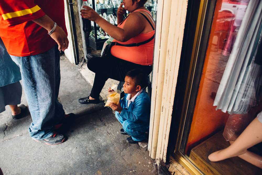 A young boy eats a snack near La Lagunilla market. Mexico City, Mexico.