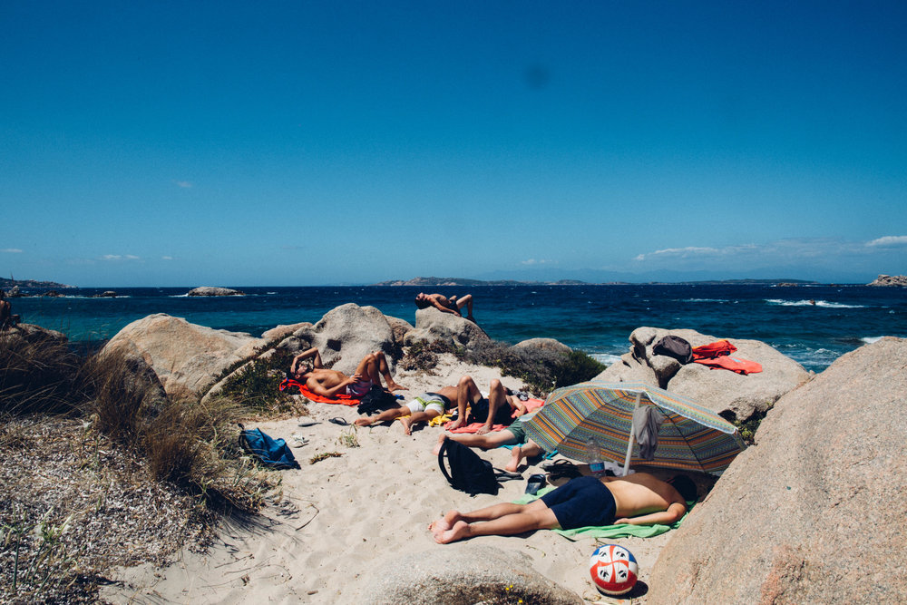 Beachgoers nap at Spiaggia Bassa Trinita in La Maddalena, Sardinia.