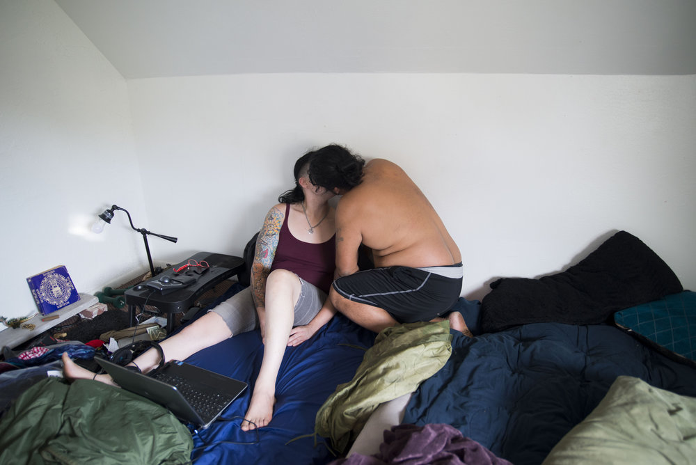 Tino Enriquez kisses his partner Claire Odette in their attic room in Lakewood, Ohio on October 4, 2017. Claire moved from Pittsburgh to Cleveland so she could be in a polyamorous relationship with Tino and three other women.