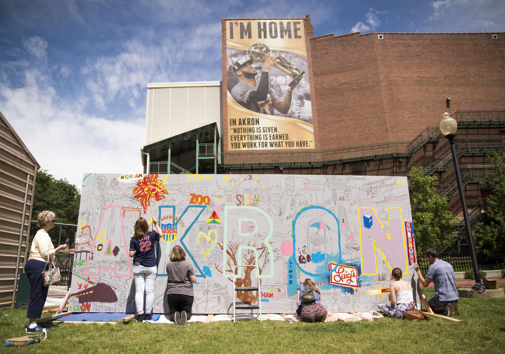 Artist Mac Love presents his Akron themed mural to the Signal Tree festival on July 29, 2017 at Lock 3. The artist encouraged community members to help fill in his mural with paint (Keown   akronist.com).