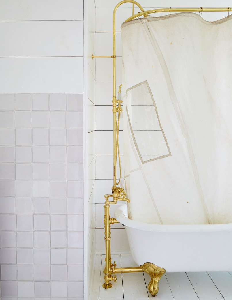 Exposed brass plumbing fixtures compliment the beauty and functionality of a cast iron tub in this bathroom designed by Leanne Ford.  Photo: Nicole Franzen