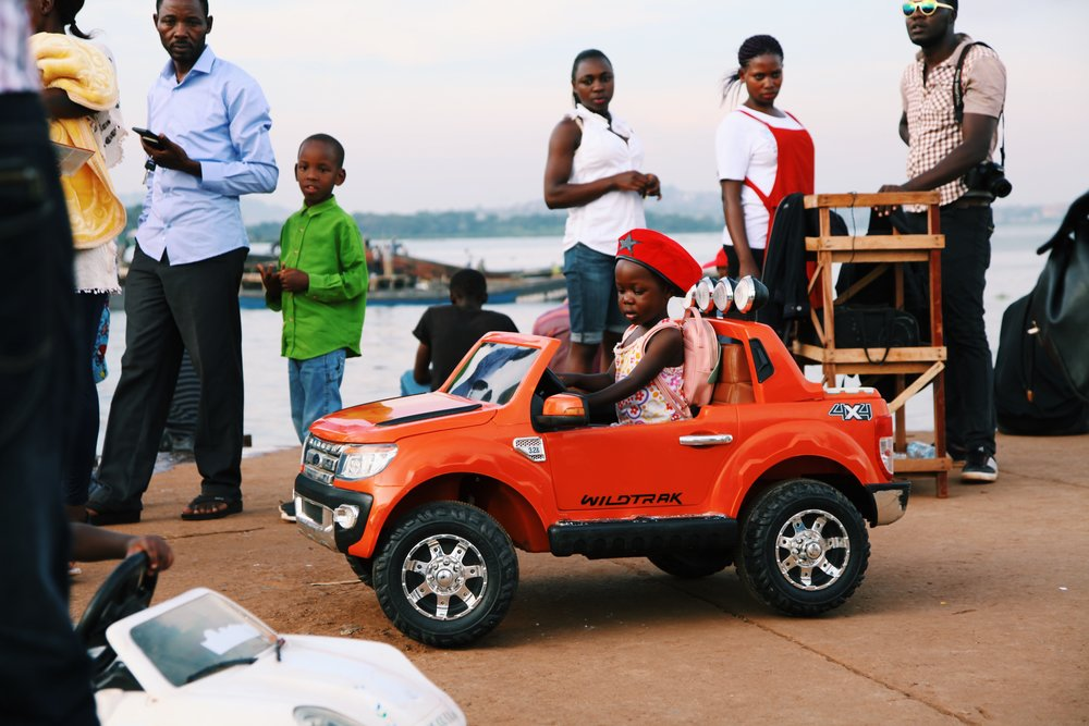A girl with Bobbi Brown hat drives car at Ggaba Market by Joost Bastmeijer.JPG