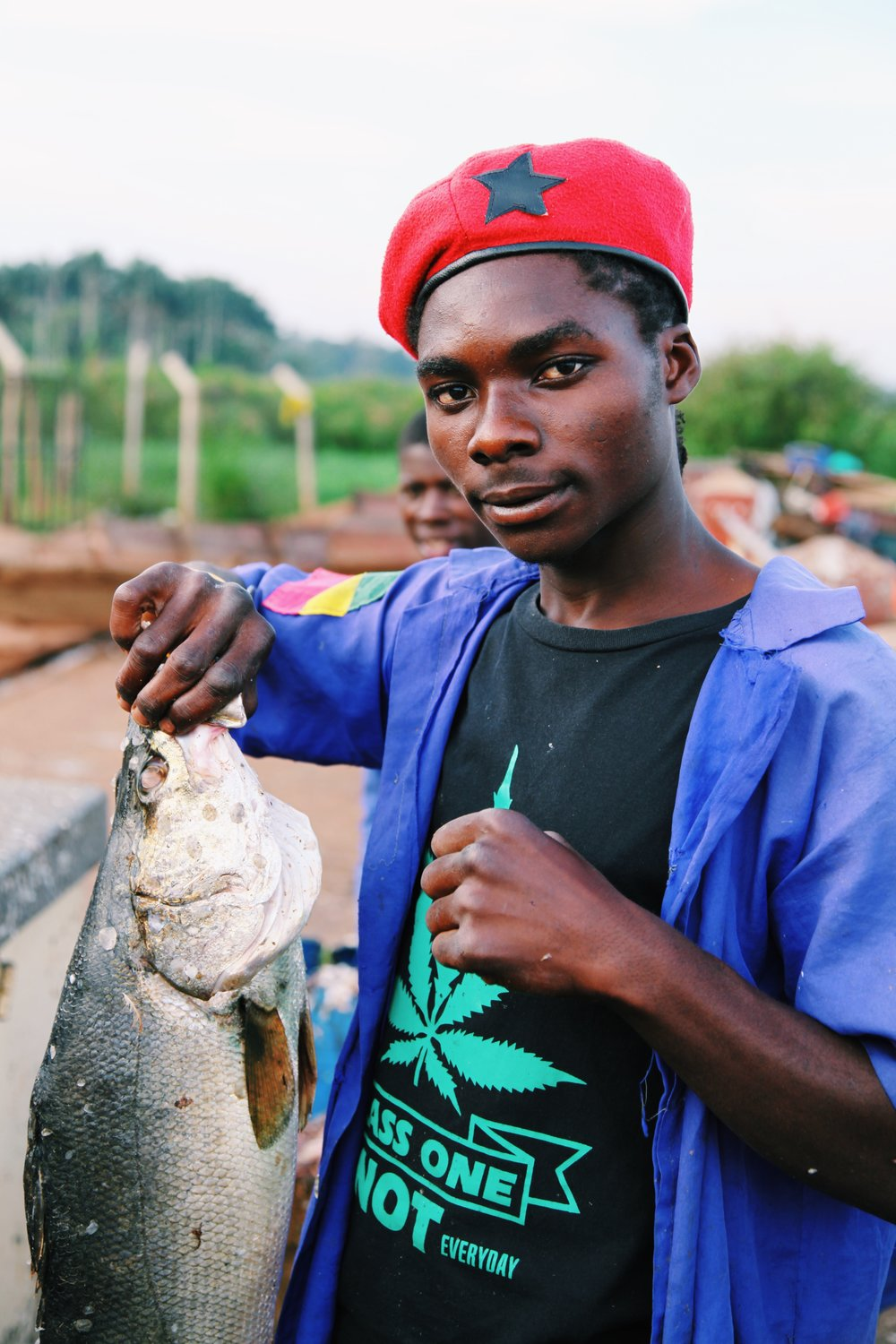A man poses with a fish at Ggaba Beach by Joost Bastmeijer.JPG