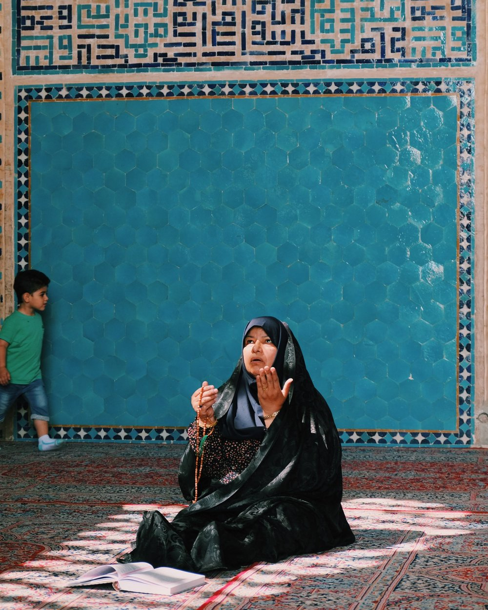 A woman prays in Yazd's mosque, a child plays in the background.jpg
