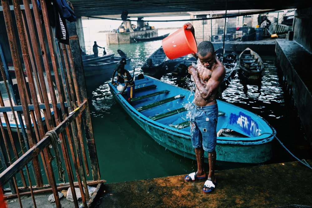 A man washes himself under a bridge turned harbour in Lagos Nigeria.JPG