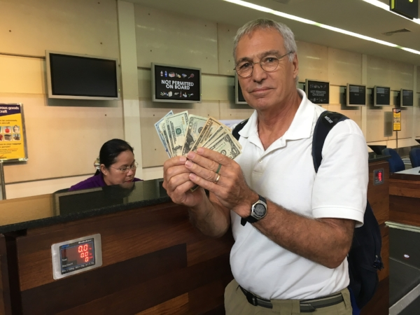 The currency in Cambodia is the US Dollar. Here is Michael handing over the ransom of $175 crisp US Dollars to get our luggage on board our flight.
