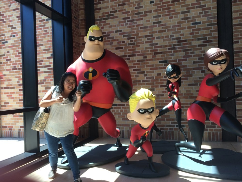 Dr. Melanie posing with The Incredibles at Pixar Animation Studios