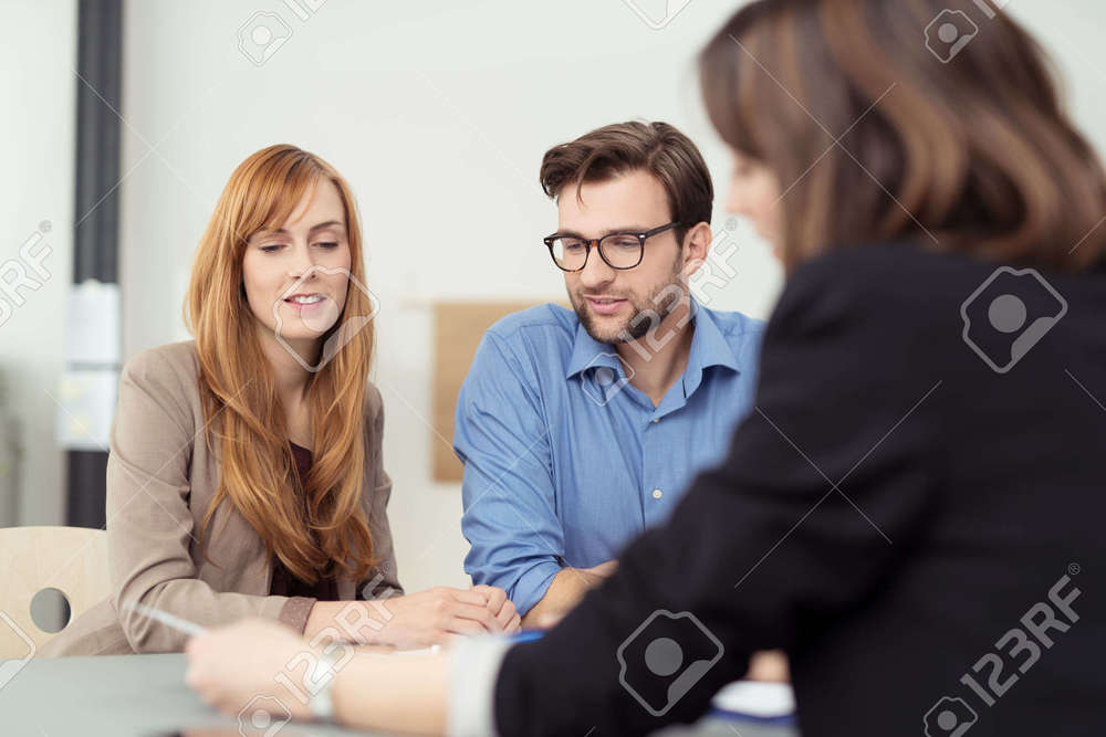 40290936-Broker-making-a-presentation-to-a-young-couple-showing-them-a-document-which-they-are-viewing-with-s-Stock-Photo.jpg