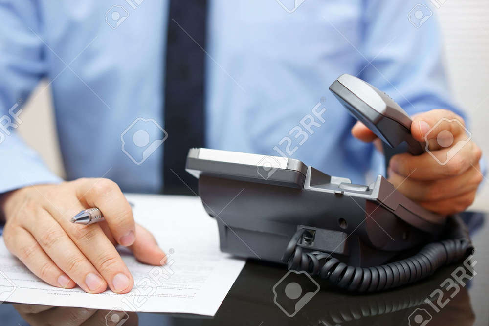 33943942-Businessman-is-picking-up-the-headset-for-help-while-reading-legal-document-Stock-Photo.jpg