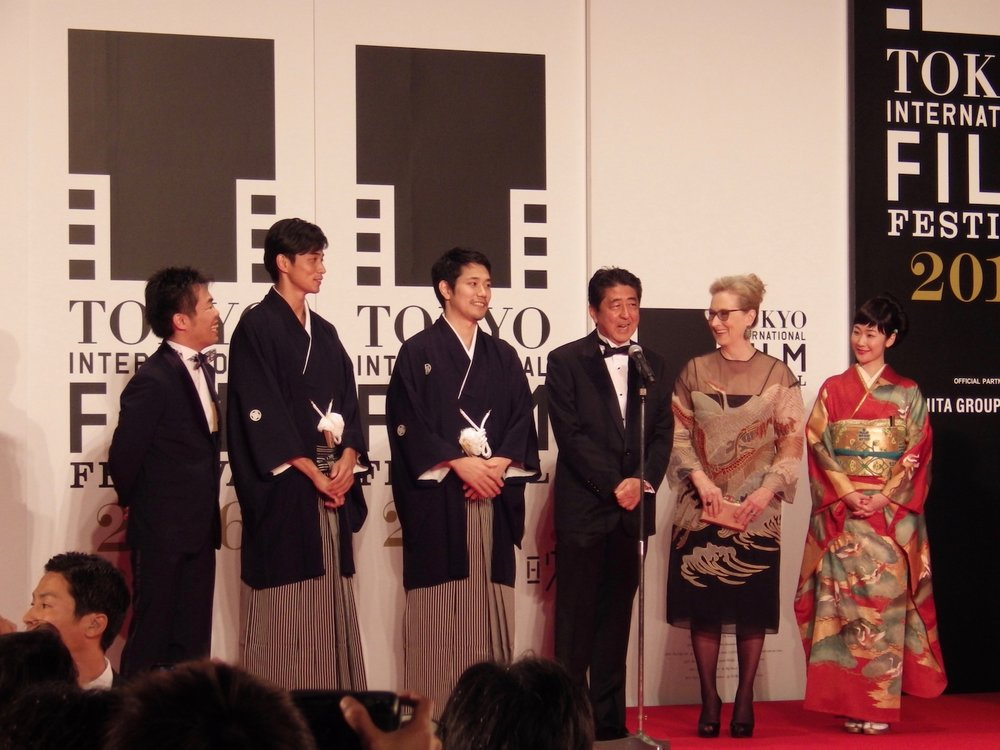 Japanese Prime Minister Shinzo Abe speaks into a microphone on stage, while actress Meryl Streep and other festival VIPs look on, at TIFF 2016.