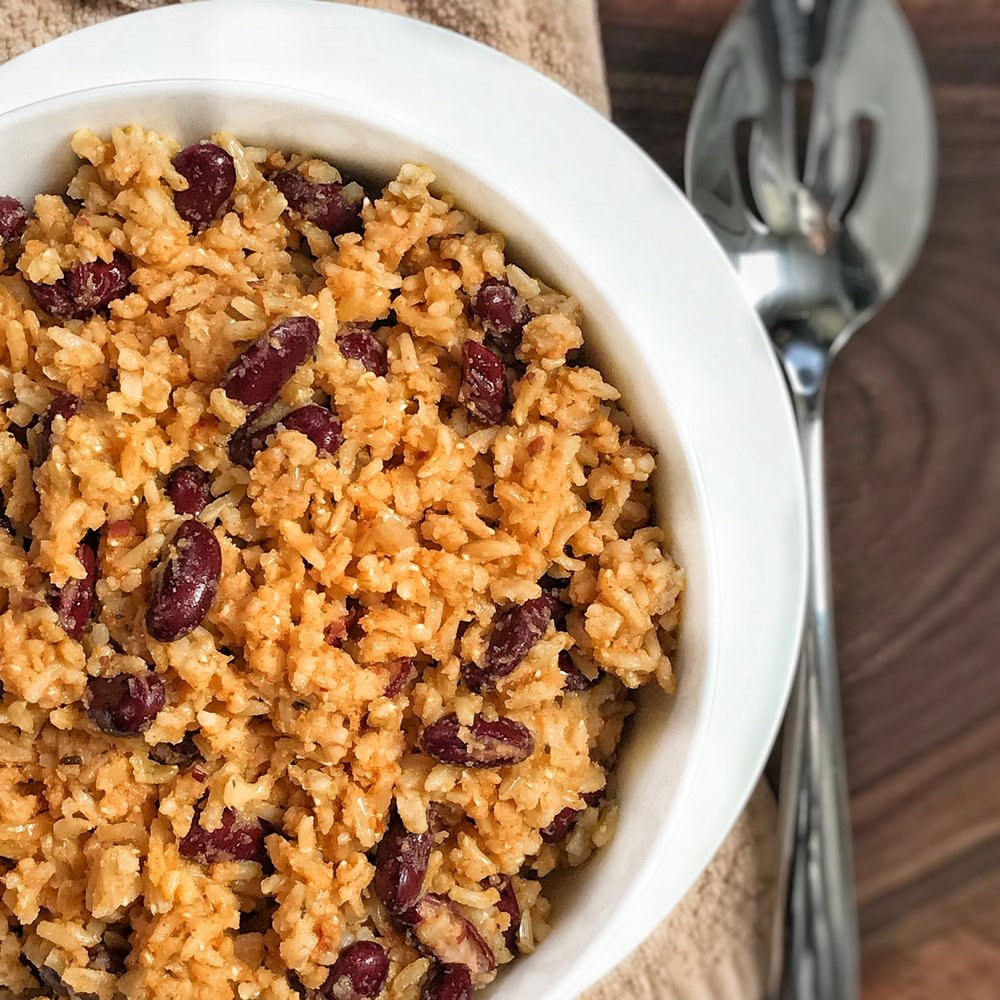 [Photo Description: Creole Rice and Beans in a round bowl on a wooden board with a serving spoon in the left]